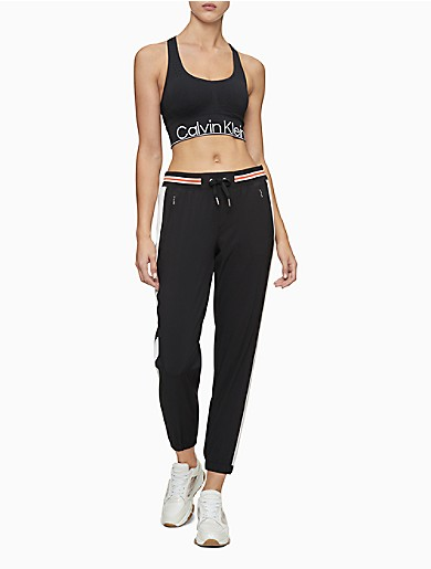 Optimized for performance, these activewear joggers are engineered with a 4-way stretch blend for total flexibility. Designed with a fitted silhouette, a drawstring elasticated striped waist, front zip pockets, side colorblock stripes, elasticated cuffs and a 7/8 length.