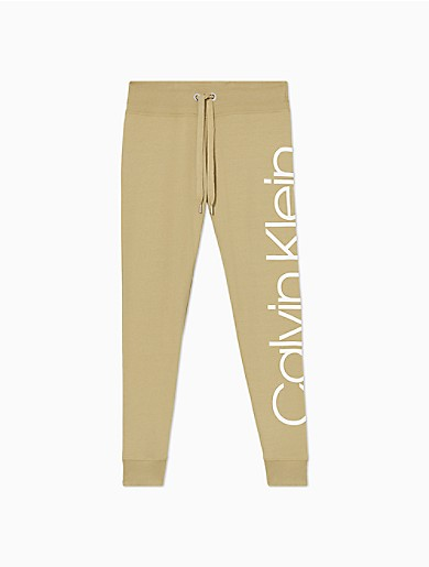 Crafted from a plush cotton knit blend for premium loungewear comfort, these signature joggers are updated with an oversized logo print. Features a high waist, front slip pockets, a slightly cropped 7/8 length and ribbed knit trim for a fine fit.