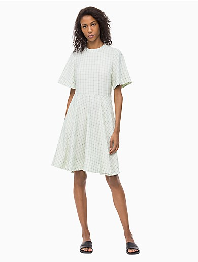 heritage-inspired with a modern silhouette, this short sleeve dress is made with fine crepe de chine and an allover check. finished with a crewneck, a keyhole closure at the back, a concealed side zip closure and a bias-cut circle skirt.