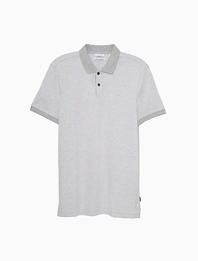 Designed with ultra-fine feeder stripes and contrast trim, this Calvin Klein polo shirt features refreshed, sporty styling with a tailored, slim fit cut. Crafted from soft cotton for excellent breathability, this essential look is detailed with a contrast collar, a button-front, a woven side seam logo tag and a vented hem for an effortless fit. Perfect for the tennis court or can be easily dressed up for a warm-weather special occasion.