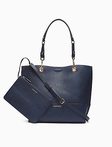 With a reversible design, this streamlined tote bag is made with a textured faux leather. Finished with dual detachable handles, a magnetic closure, an adjustable shoulder strap and subtle logo detailing. Comes with a top zip logo pouch.