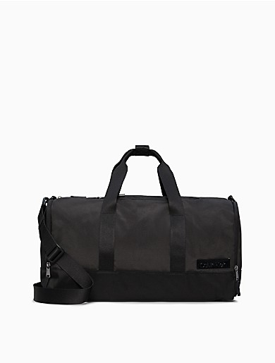 Designed with durable nylon and casual styling, this versatile duffle bag features throughly modern detailing and antique nickel hardware. Made with dual carry handles and a snap tab, a detachable crossbody strap, a top zip closure, side zippered compartments, a signature logo plaque at front and ample interior storage space.