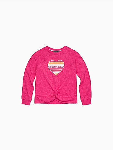 With a unique twist-front design at the hem, this chic girls long sleeve sweatshirt is made with a cotton knit blend for premium comfort, a classic crewneck, long raglan sleeves and a striped logo heart at the center.